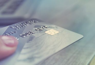 Woman hand holding credit card. Close up. Selective focus.
